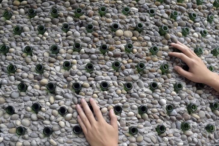 Una pared hecha con botellas, piedras y cemento