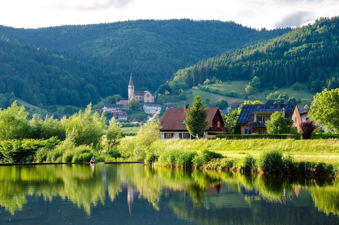 fotos paisajes hermosos y verdes del mundo: casas al lado de un lago con montañas de fondo