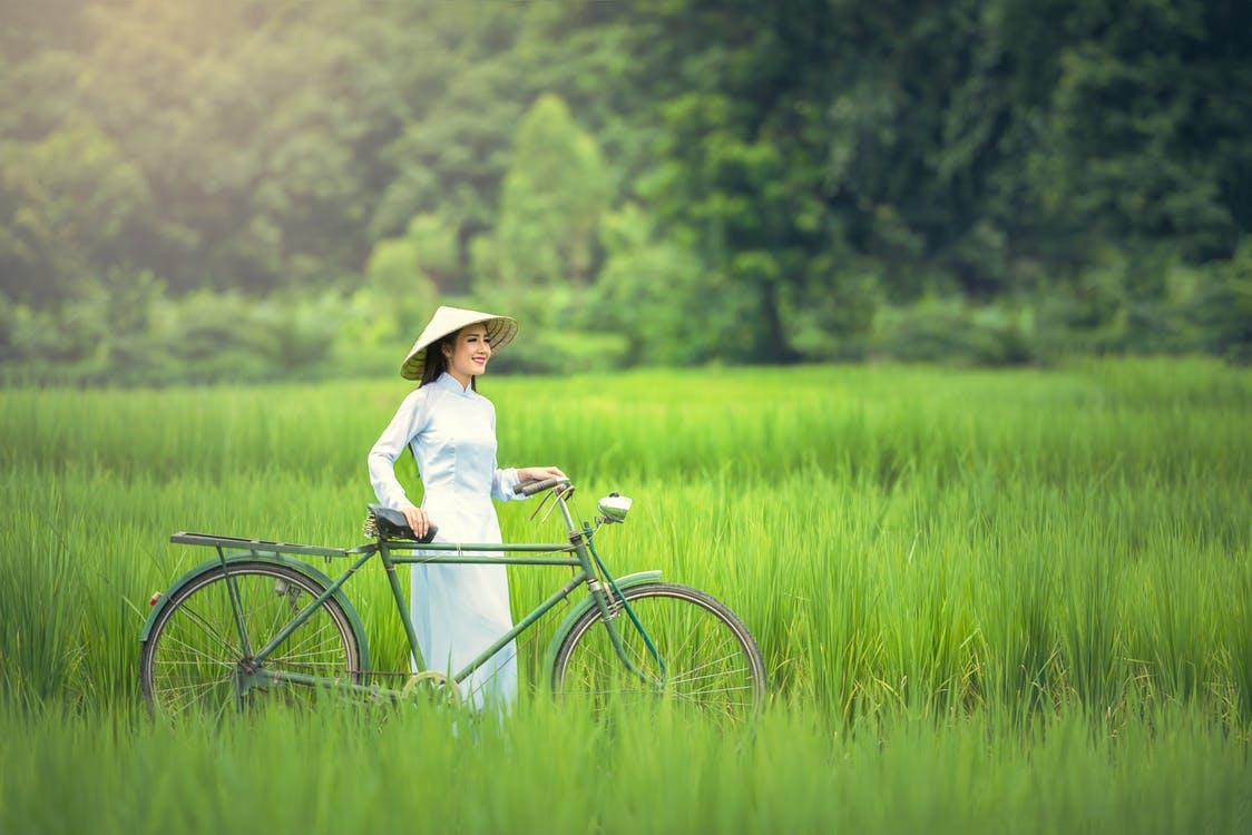 Una mujer asiática contempla la hermosa naturaleza en esta fotografía en un campo de cultivo